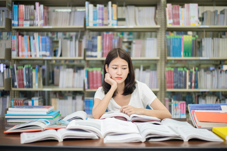 disheartened: Asian woman student boring reading book at library with a lot of books in university. Asian student disheartened reading book for examination.