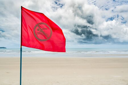 Red no swimming flag warning for tourist not to swim during storm coming in the sea.