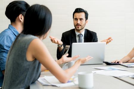 Negoziazione di affari, soci maschii che discutono, donna easygoing divertente che mantiene calma nella situazione di sollecitazione, meditante con il sorriso composto, occupandosi del cliente arrabbiato emozionale, concetto di gestione dello stress Archivio Fotografico - 83151701