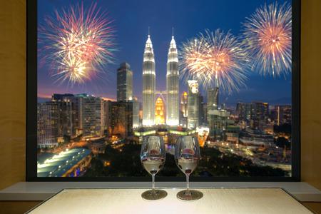 Closeup of a glasses of red wine at windowsill, against night Kuala lumpur city view of urban city sky line blurring lights. Malaysia. Banco de Imagens