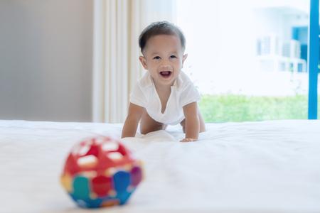 Crawling baby boy sul letto in camera da letto in casa e lui sorriso a te, bambino asiatico. Archivio Fotografico - 83538895