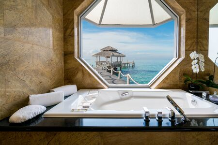modern bathroom: Luxury beautiful interior design on beach resort, window view from bathroom on clear blue sea, summer vacation in Phuket, Thailand. Summer, Travel, Vacation and holiday concept.