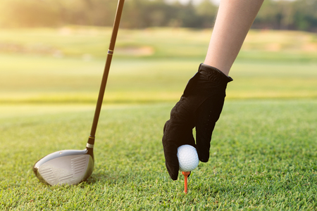 Hand placing a tee with golf ball. Hand hold golf ball with tee on course, close-up