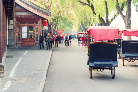 Tourists riding Beijing traditional rickshaw in old China Hutongs in Beijing, China.