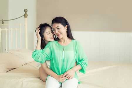 Asian mother and adult daughter hugging and having fun together in bedroom at home. Portrait of happy women smiling and looking at the camera.