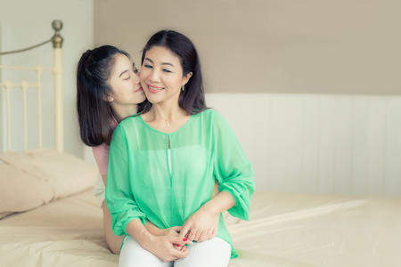 Asian love of mother and daughter. Happy woman in bedroom with copy space. Aged woman and her adult daughter kissing at bedroom in house. Mothers day. Stock Photo