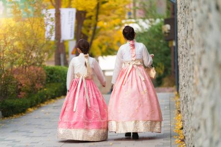 Asian Korean woman dressed Hanbok in traditional dress walking in Jeongdong-gil in Seoul, South Korea.