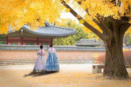 Asian Korean woman dressed Hanbok in traditional dress walking in Gyeongbokgung Palace in autumn season at Seoul, South Korea.