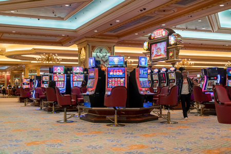 Macau, China - October 15, 2017: Arcade machine and gamblers inside The Venetian Casino in Macau. Macau is the capital of casinos and Asian gambling and, now, in the world.