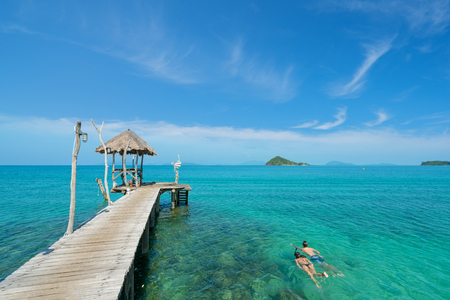 Young couple of tourists snorkel in crystal turquoise water near tropical resort in Phuket, Thailand. Summer, Vacation, Travel and Holiday concept.