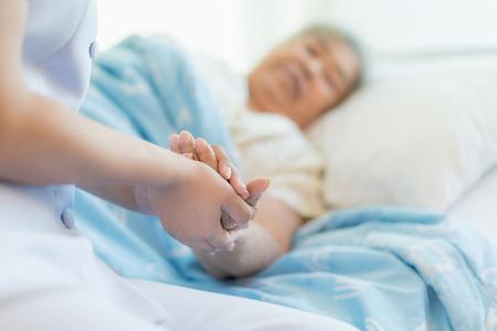 De verpleegsterszitting op een het ziekenhuisbed naast een oudere vrouw die handen helpen, geeft voor het bejaarde concept