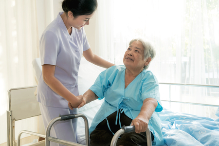 Asian young nurse supporting elderly patient disabled woman in using walker in hospital. Elderly patient care concept.  Banco de Imagens