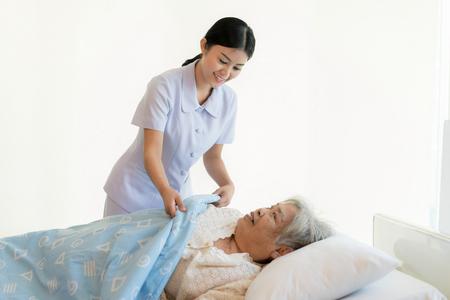 Asiatische Krankenschwester in der Altenpflege bedecken sie mit einer Decke für ältere Menschen im Pflegeheim.