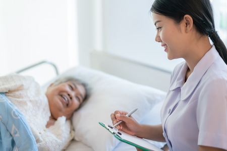 Asian nurse checking up the history of the disease elderly patient lying in bed. Nurse cares for a elderly woman. Imagens