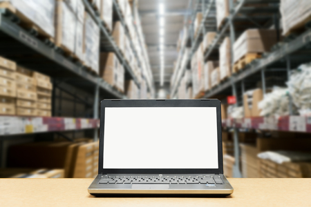 Laptop with white blank screen on brown wooden desk and blurred warehouse store background  Stok Fotoğraf