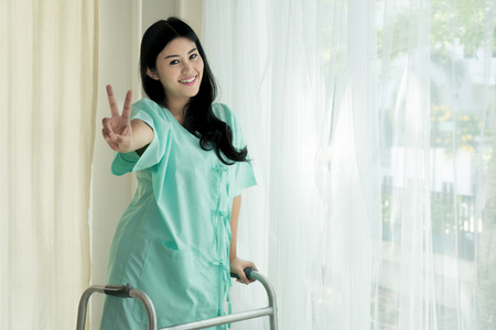 Young Asian patient woman standing with Folding walker at hospital room showing victory sign for cheerful. Archivio Fotografico