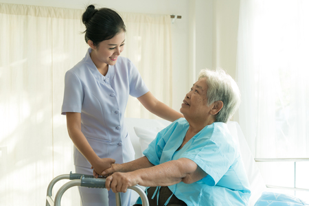 Asian young nurse supporting elderly patient disabled woman in using walker in hospital. Elderly patient care concept.  Reklamní fotografie