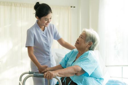 Aziatische jonge verpleegster ondersteunend bejaarde patiënt gehandicapte vrouw in het gebruiken van leurder in het ziekenhuis. Oudere patiëntenzorg concept.