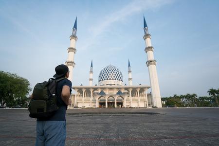 Young man traveler with backpack walking to Salahuddin Abdul Aziz Shah Mosque at Shah Alam, Selangor, Malaysia. Stok Fotoğraf