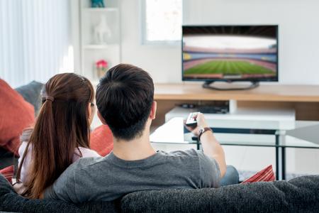 Vista trasera de una pareja asiática viendo fútbol en la televisión en la sala de estar. Concepto de festival de fútbol. Foto de archivo