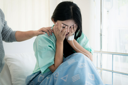 Asian young woman patient receiving bad news, Woman patient is desperate and crying. Her Mother support and comforting her patient with sympathy. 写真素材