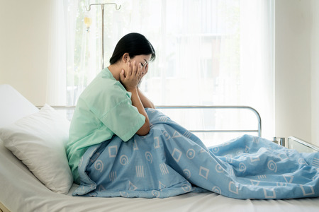 Asian young woman patient lying at hospital bed feeling sad and depressed worry. Disease feeling sick in health care and clinical attention concept.