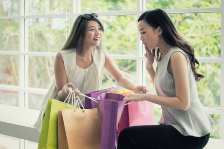 Young Asian woman in shopping mall hold shopping bag and looking in bag and surprise with wonderful beauty fashion accessories, clothes, makeup in packages