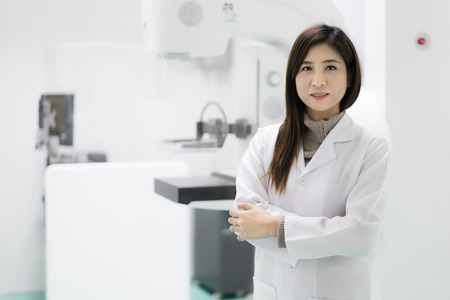 Young Asian female radiologist doctor standing near mammogram ultrasound medical scan in hospital.