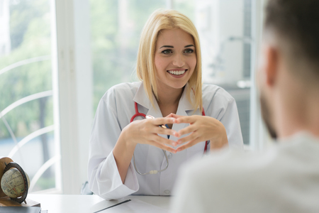 Doctor consulting male patient, working on diagnostic examination on mens health disease or mental illness, while writing on prescription record information document in clinic or hospital office