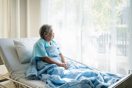 Asian depressed elderly woman patients lying on bed looking out the window in hospital. Elderly woman patients is glad recovered from the illness. Stockfoto - 106138706