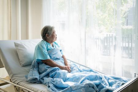 Aziatische depressieve oudere vrouw patiënten liggend op bed kijkt uit het raam in het ziekenhuis. Patiënten met een oudere vrouw zijn blij dat ze hersteld zijn van de ziekte.