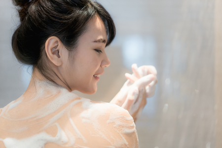 Young Asian woman taking a shower in the bathroom with Shower head. Looking happy and relax. Imagens