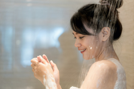 Young Asian woman taking a shower in the bathroom with Shower head. Looking happy and relax. Archivio Fotografico