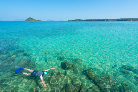 Tourists snorkel in crystal turquoise water near tropical resort in Phuket, Thailand. Summer, Vacation, Travel and Holiday concept. 写真素材