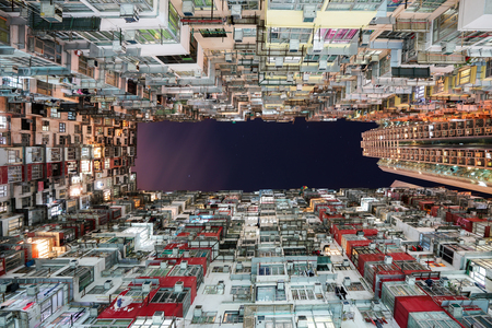 Hong Kong city residences area. Low angle view image of a crowded residential building in community in Quarry Bay at night, Hong Kong