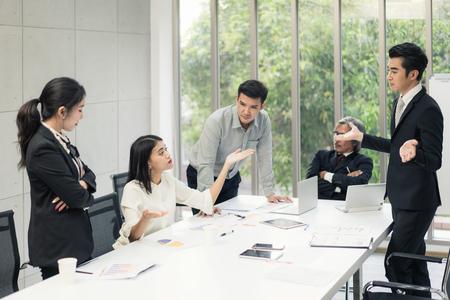 Negociación comercial, socios masculinos discutiendo, divertida mujer tranquila que mantiene la calma en una situación estresante, meditando con una sonrisa compuesta, tratando con un cliente enojado emocional, concepto de manejo del estrés Foto de archivo