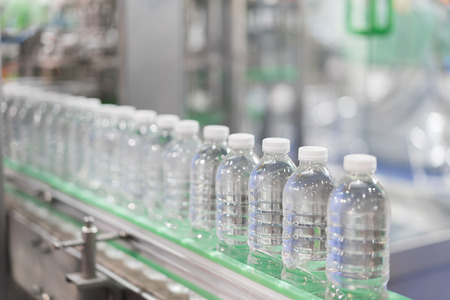 Clear Water Bottles transfer on Conveyor Belt System. Industrial and factory with machine technology concept.