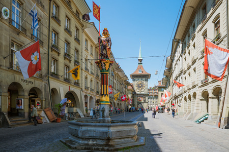 Shopping street with clock tower Zytgloggein the old medieval city of Bern, Switzerland.