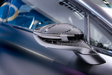 Silver side view mirror with silver modern car. Close up.