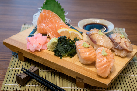 Mixed salmon sushi on wooden plate along with Japanese sauce and green leaf decoration, Japanese food, close up at sushi .