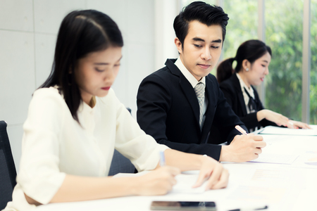 Inquisitive curious businessman with bad manners sneakly looking at report of businesswoman trying to steal idea of competitor, copying work at corporate exam, gathering information on rival. 写真素材