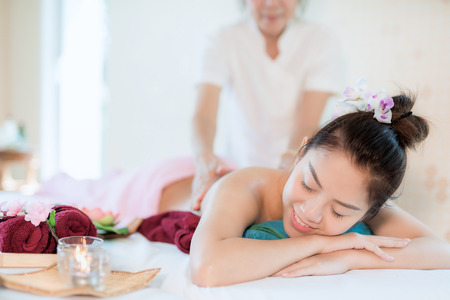 Mujer asiática Yougn relajante con masaje de manos en el salón de belleza spa. Foto de archivo