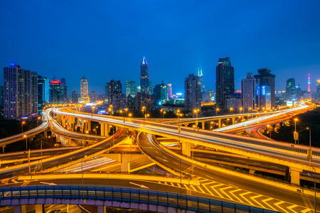 Shanghai elevated road junction and interchange overpass at night in China. Фото со стока