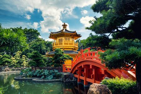 Vista frontal del templo del pabellón dorado con puente rojo en el jardín Nan Lian, Hong Kong. Asia. Foto de archivo