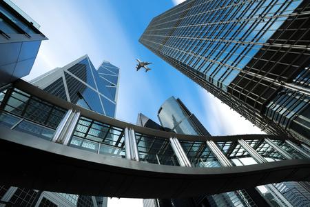 香港のモダンビジネスセンター。香港で上空を飛ぶ飛行機と商業地域の超高層ビル。アジア