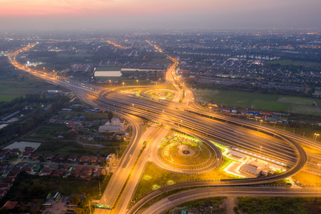 Aerial view of highway junctions. Bridge roads shape number 8 or infinity sign in structure of architecture concept. Top view. Urban city, Bangkok at night, Thailand.