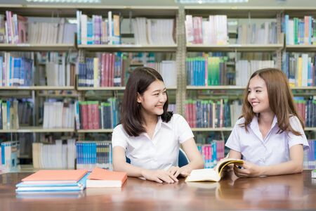 Two Asian students studying together in library at university. University student. Stock Photo