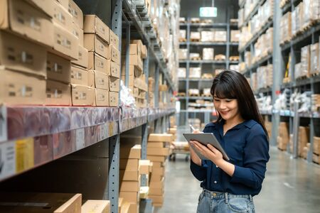 Young asian woman auditor or trainee staff work looking up and checks the number of items store by digital tablet. Asian owner or small business concept.