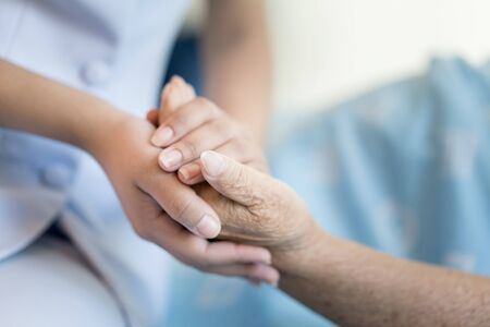 Enfermera sentada en una cama de hospital junto a una mujer mayor que ayuda a manos, cuidado del concepto de ancianos