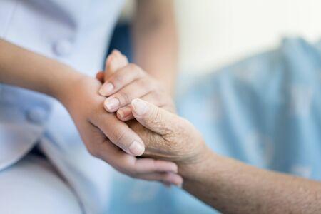 Verpleegkundige zittend op een ziekenhuisbed naast een oudere vrouw die handen helpt, zorg voor ouderen concept